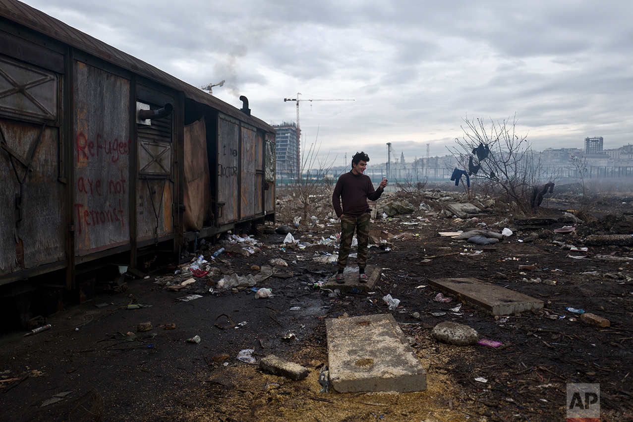 An Afghan refugee speaks on a mobile phone outside an old train carriage where he and other migrants took refuge in Belgrade, Serbia, Thursday, Feb. 2, 2017. (AP Photo/Muhammed Muheisen)
