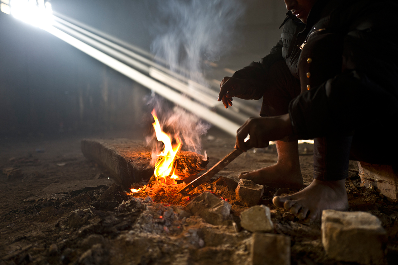 An Afghan refugee youth warms his legs and hands around a fire in an abandoned warehouse in Belgrade, Serbia, Monday, Jan. 30, 2017. (AP Photo/Muhammed Muheisen)