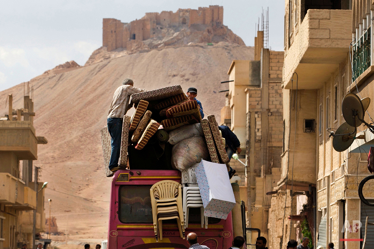 In this picture taken Thursday, April 14, 2016, the Palmyra citadel is seen in the background as Syrian families load their belongings onto a bus in the town of Palmyra in the central Homs province, Syria. Thousands of residents of this ancient town who fled Islamic State rule are returning briefly to check on their homes and salvage what they can - some carpets, blankets, a fridge or a few family mementos. (AP Photo/Hassan Ammar)