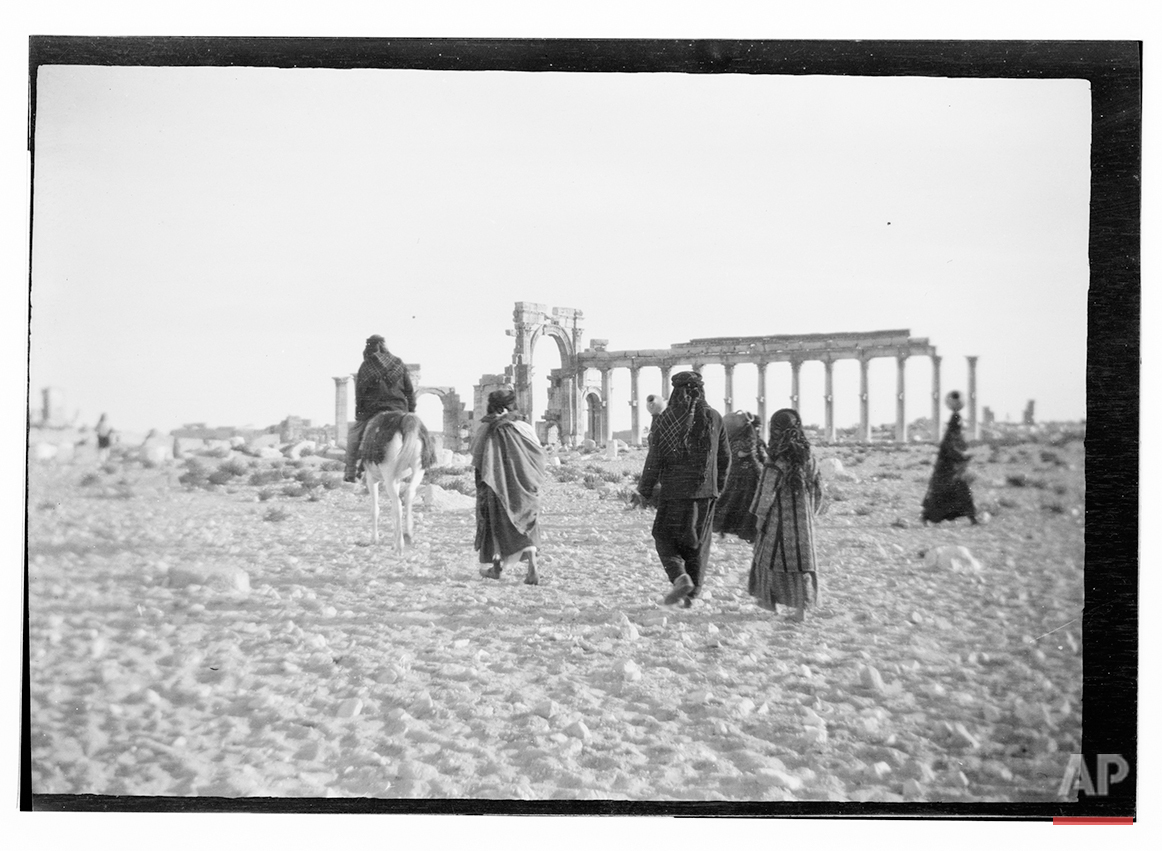 In this undated photo, believed to have been made between 1925 – 1946, people are shown near the ruins of the ancient city of Palmyra in the central Homs province, Syria. (Library of Congress via AP)