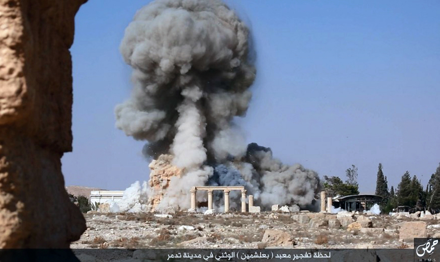 This undated photo released Tuesday, Aug. 25, 2015, photo, on a social media site used by Islamic State militants, which has been verified and is consistent with other AP reporting, shows smoke from the detonation of the 2,000-year-old temple of Baalshamin in Syria's ancient caravan city of Palmyra. (Islamic State social media account via AP)