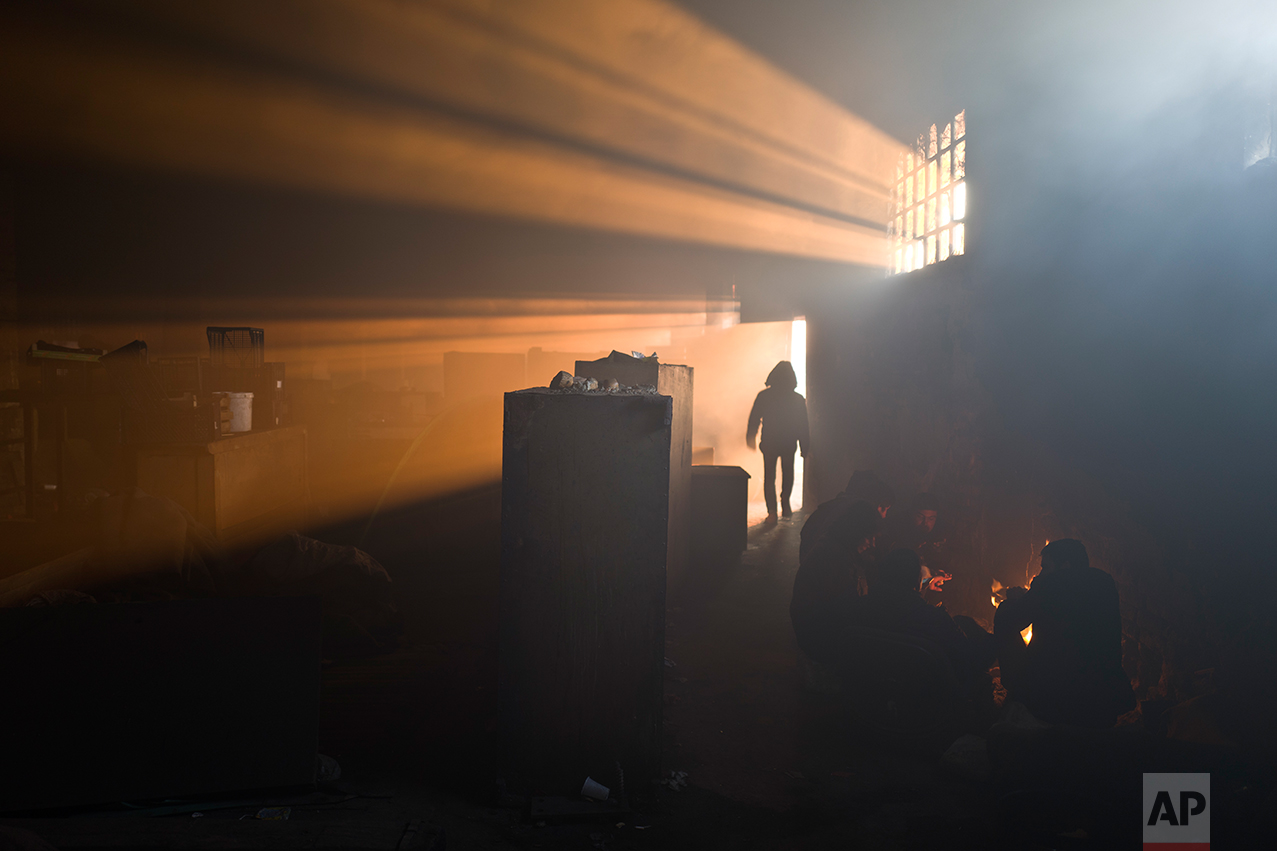 A group of migrants warm themselves by a fire in an abandoned warehouse in Belgrade, Serbia, Monday, Jan. 30, 2017. (AP Photo/Muhammed Muheisen)