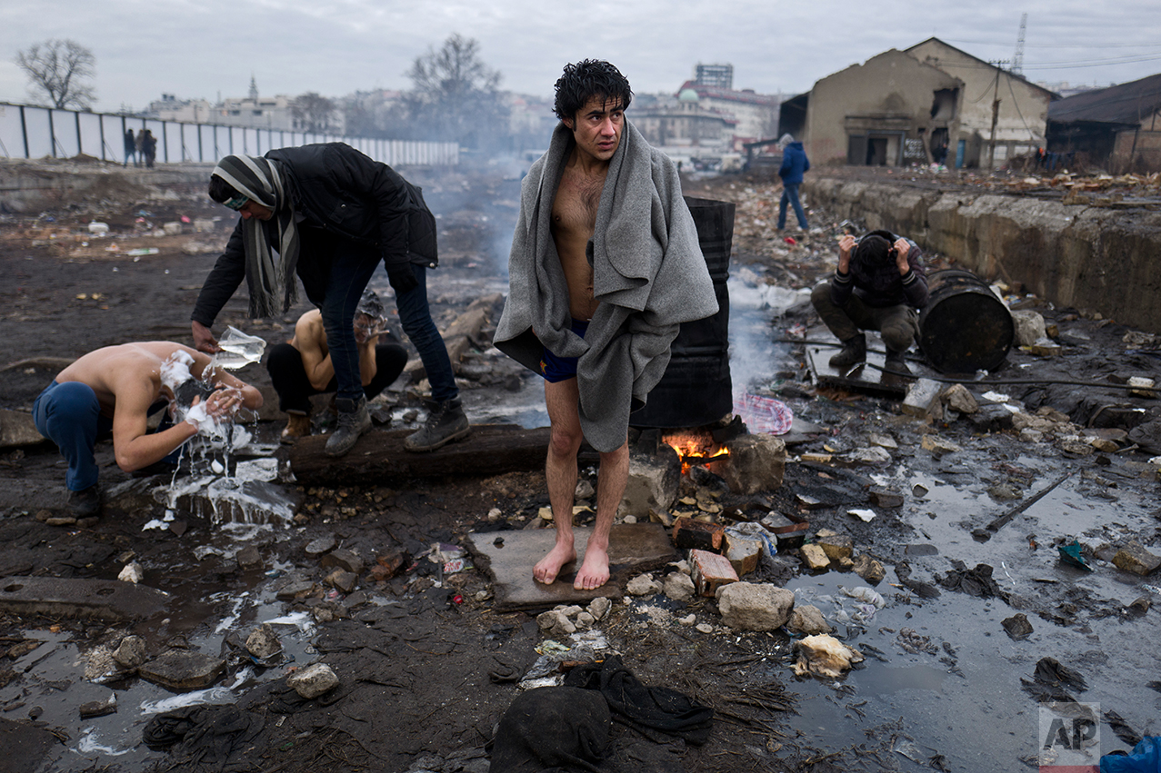 Afghan refugee men shower outside an abandoned warehouse where they are taking refuge in Belgrade, Serbia, Thursday, Feb. 2, 2017. (AP Photo/Muhammed Muheisen)
