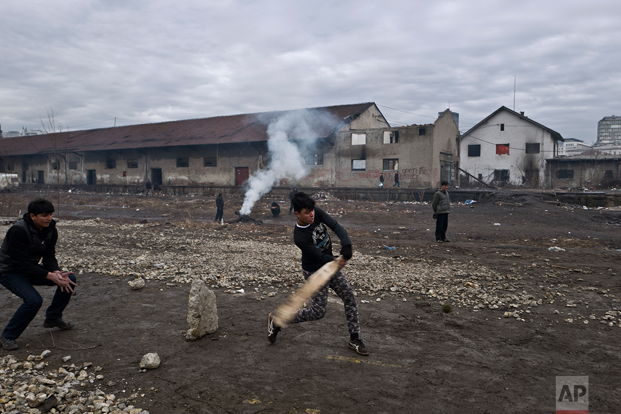 Migrants play cricket outside an abandoned warehouse where they are taking refuge in Belgrade, Serbia, Thursday, Feb. 2, 2017. (AP Photo/Muhammed Muheisen)
