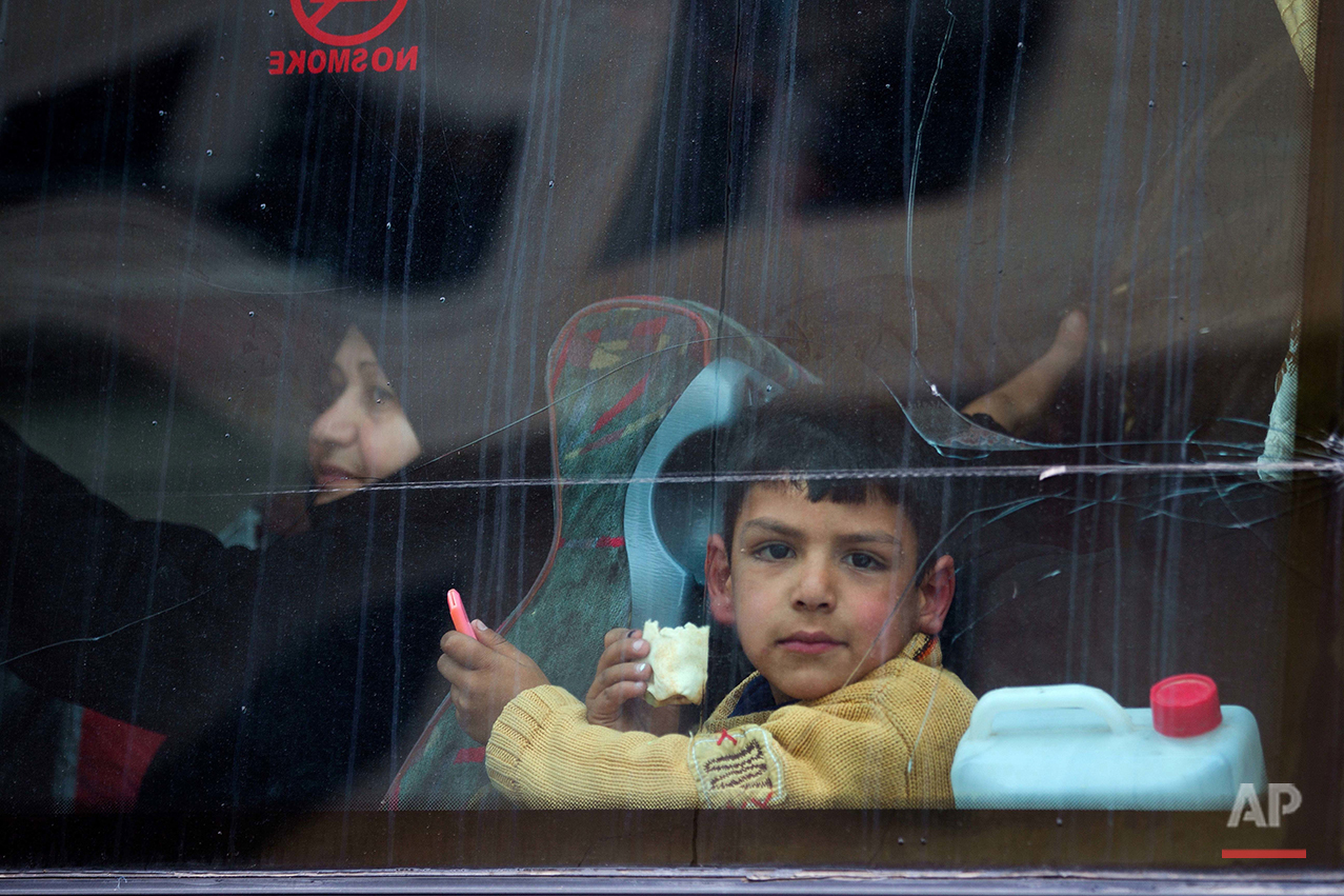 In this picture taken Thursday, April 14, 2016, a Syrian child looks through a window after his family loaded their belongings onto a bus in the town of Palmyra in the central Homs province, Syria. (AP Photo/Hassan Ammar)