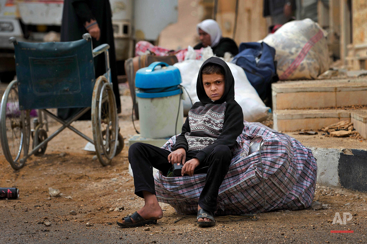 In this picture taken Thursday, April 14, 2016, a Syrian boy waits as his family to loads their belongings onto a bus in the town of Palmyra in the central Homs province, Syria. (AP Photo/Hassan Ammar)