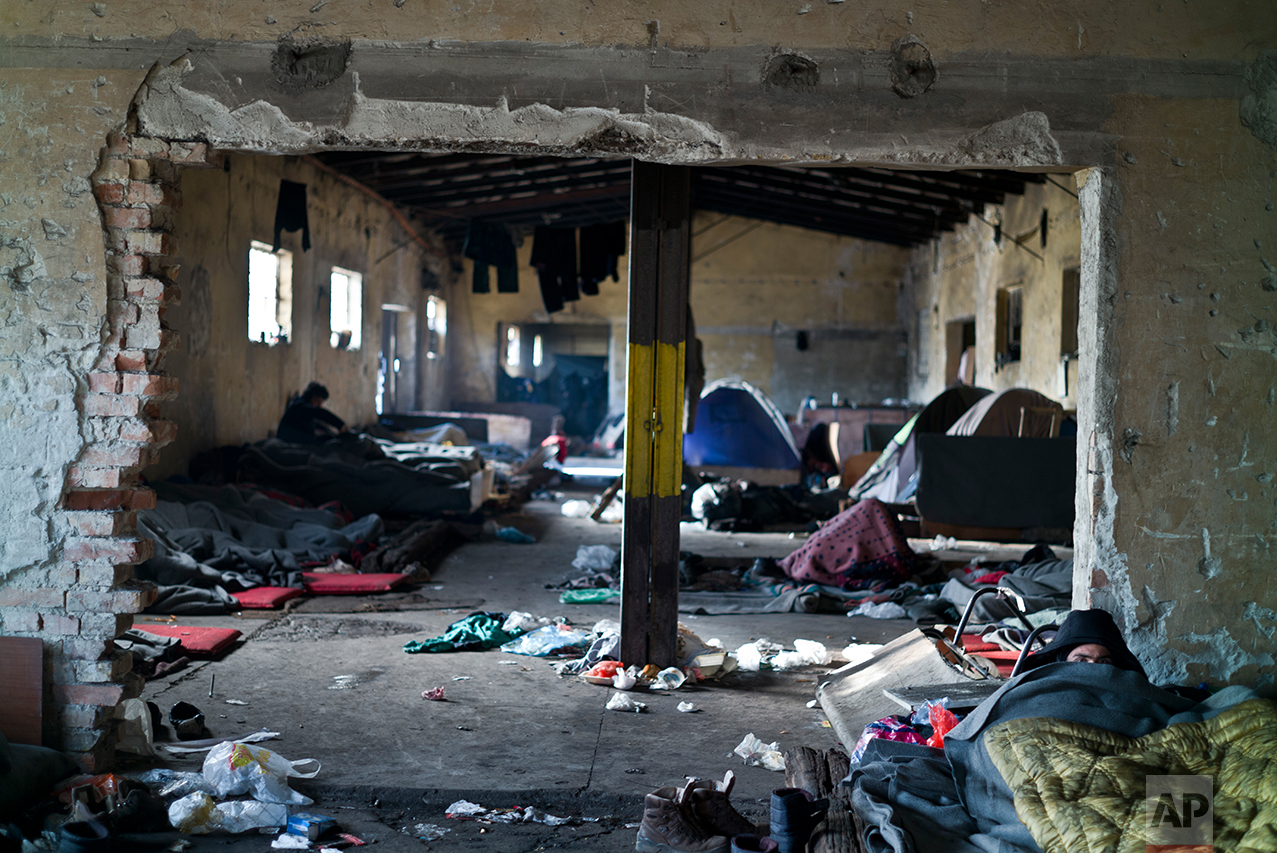 An Afghan refugee, right, lies on the ground of an abandoned warehouse where he and other migrants took refuge in Belgrade, Serbia, Tuesday, Jan. 31, 2017. (AP Photo/Muhammed Muheisen)