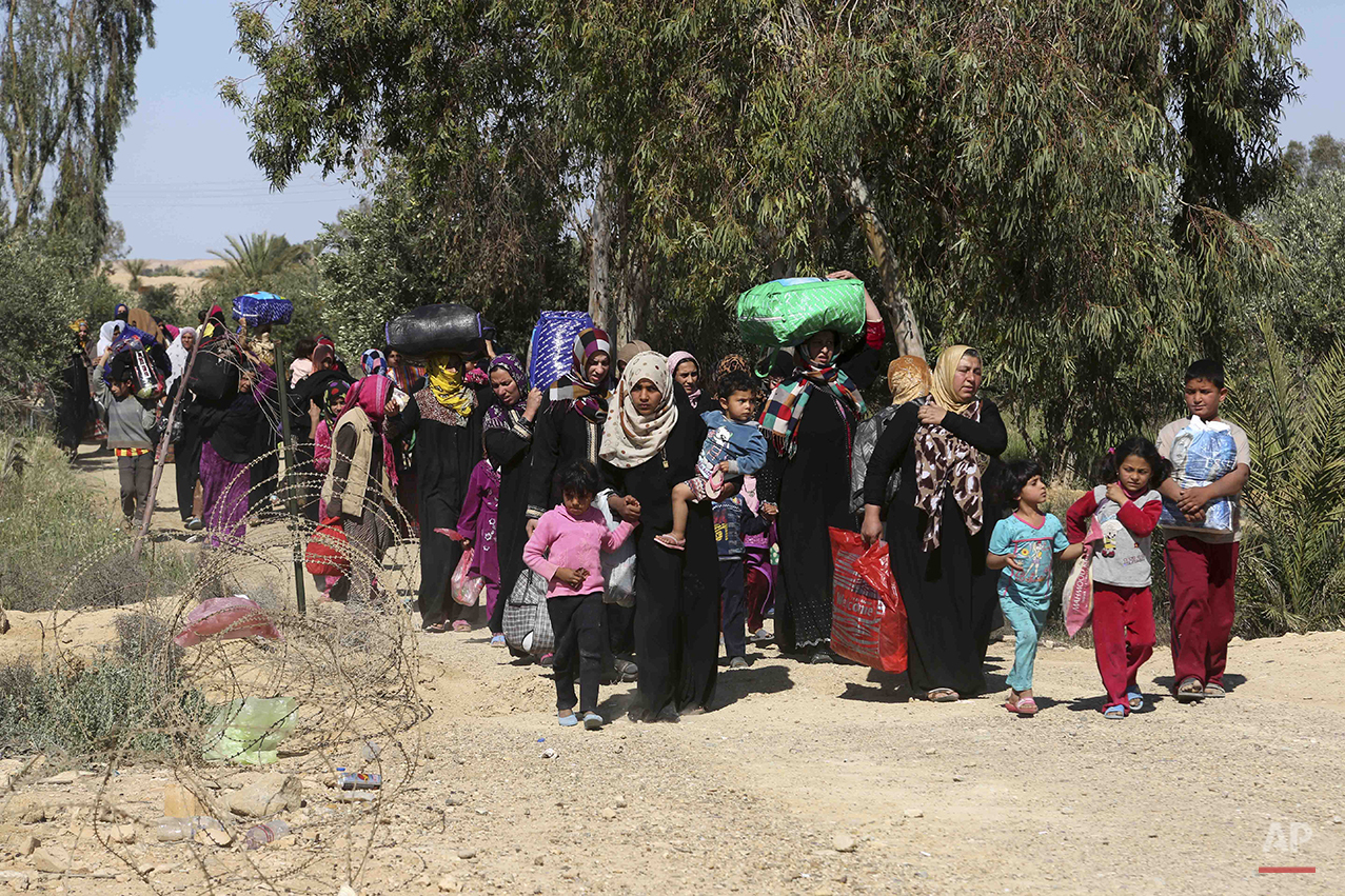 People flee their homes during clashes between Iraqi security forces and Islamic State group in Hit, 85 miles (140 kilometers) west of Baghdad, Iraq, Monday, April 4, 2016. Families, many with small children and elderly relatives say they walked for hours Monday through desert littered with roadside bombs to escape airstrikes and clashes. (AP Photo/Khalid Mohammed)