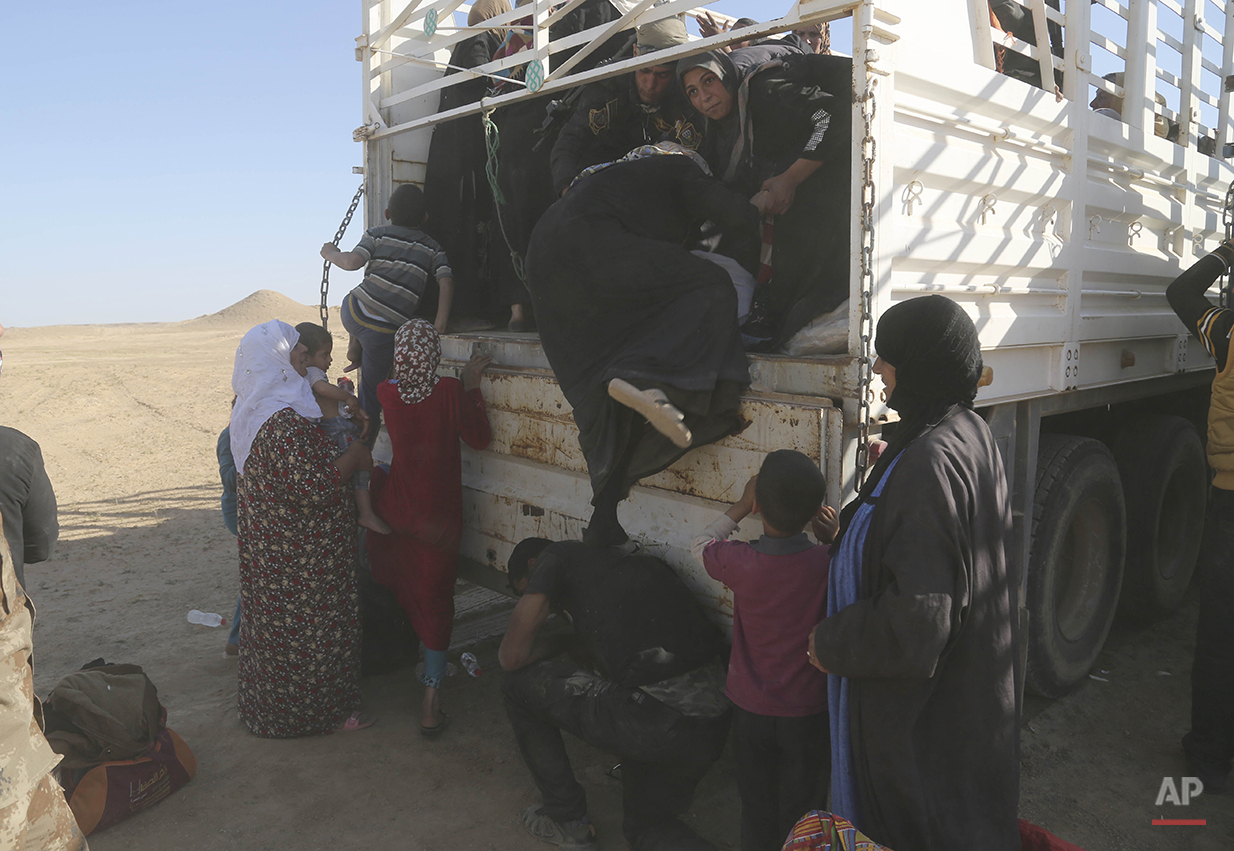 A member of elite counter terrorism forces helps women and children fleeing their homes during clashes between Iraqi security forces and Islamic State group in Hit, 85 miles (140 kilometers) west of Baghdad, Iraq, Monday, April 4, 2016. Families, many with small children and elderly relatives say they walked for hours Monday through desert littered with roadside bombs to escape airstrikes and clashes. (AP Photo/Khalid Mohammed)