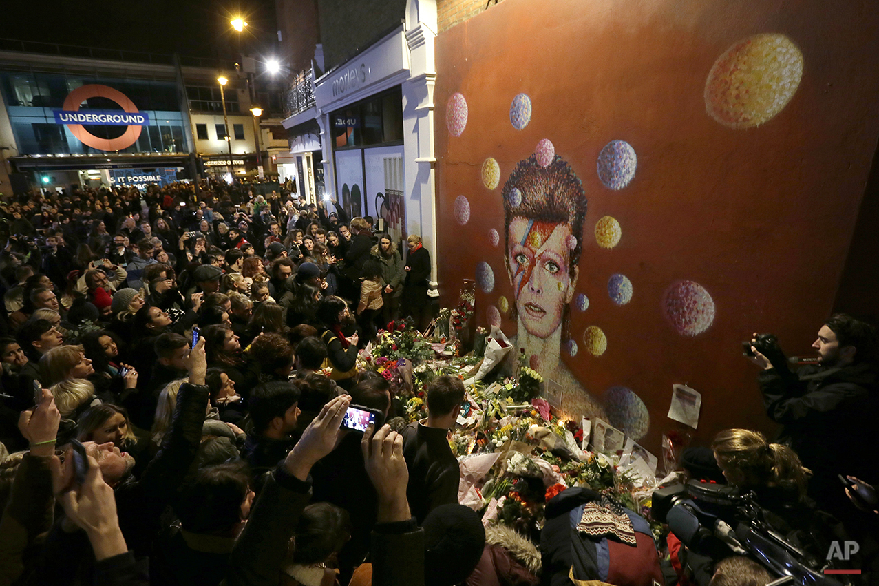 People gather next to tributes placed near a mural of British singer David Bowie by artist Jimmy C, in Brixton, south London, Monday, Jan. 11, 2016. (AP Photo/Tim Ireland)