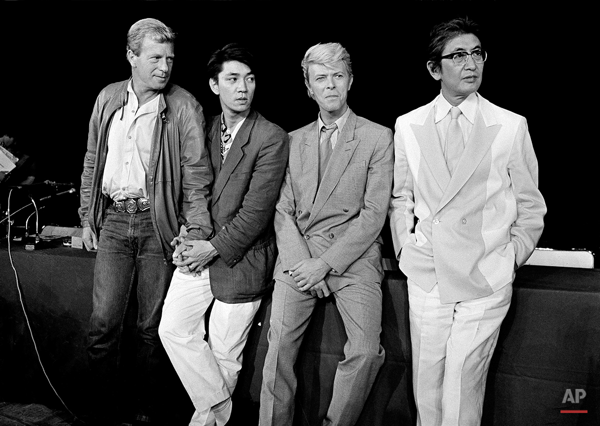 """The team that created the film """"Merry Christmas, Mr. Lawrence"""" is pictured in Paris, May 11, 1983. From left: Jack Thomas, producer; Ryuichi Sakamoto, musical composer; David Bowie, star, and Nagisa Oshima, director. (AP Photo/Jacques Langevin)"""