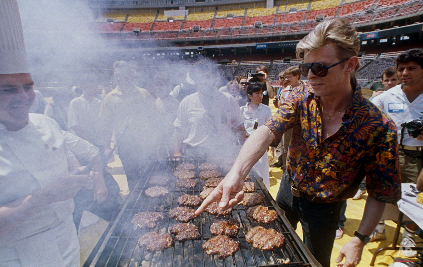 Rocker David Bowie, right, points to the hamburger that he wants for lunch during a barbecue for his crew at Veterans Stadium in Philadelphia, July 27, 1987. (AP Photo/Charles Krupa)