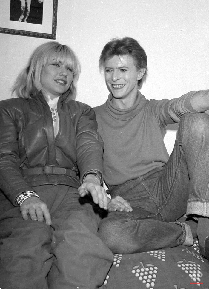 """Deborah Harry of the rock band Blondie visits David Bowie backstage at the Booth Theater where he is starring in """"The Elephant Man,"""" Nov. 1980. (AP Photo/Nancy Kaye)"""