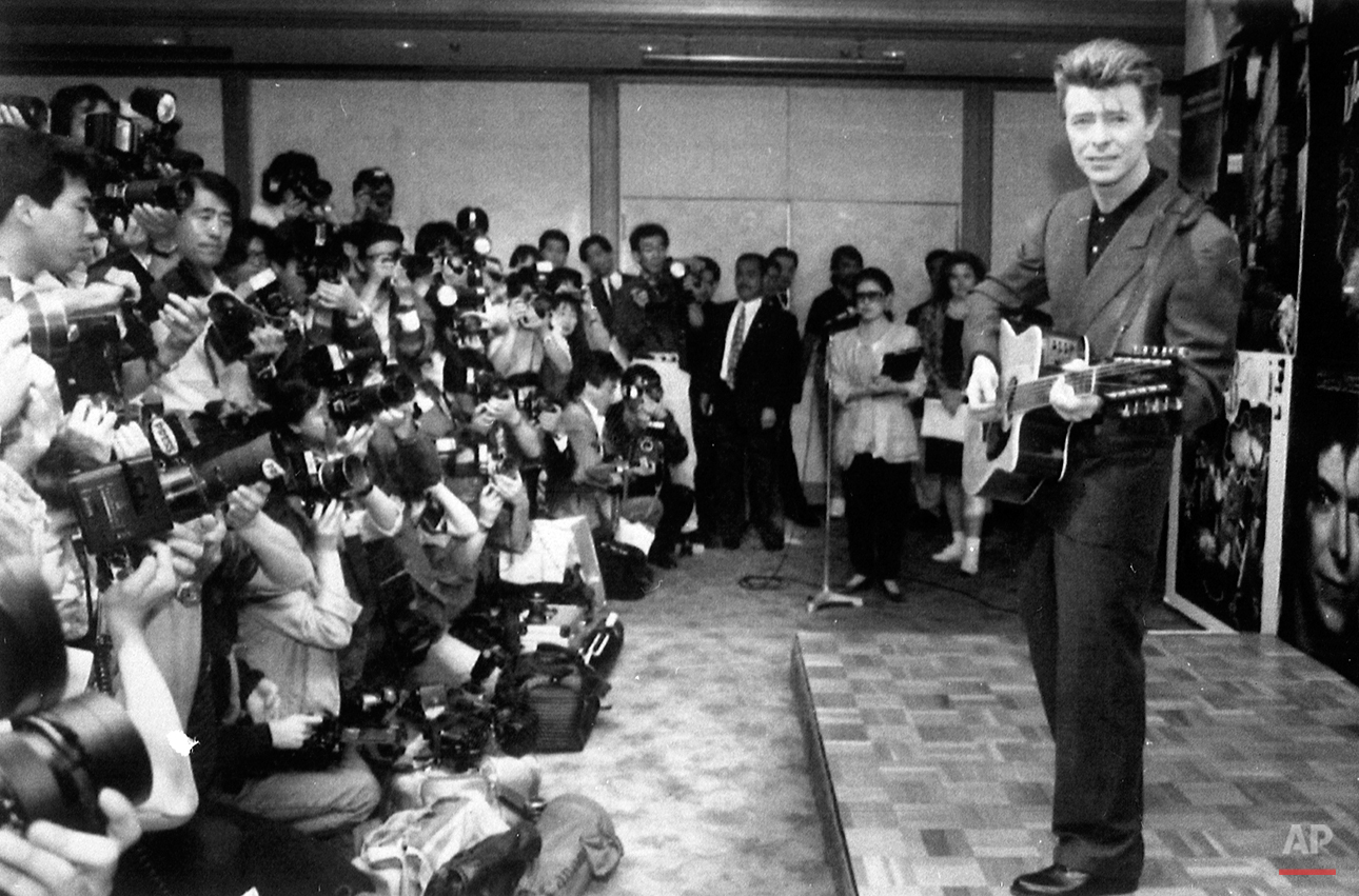David Bowie plays an acoustic guitar while being photographed at a press conference in Japan on May 19, 1990. (AP Photo)