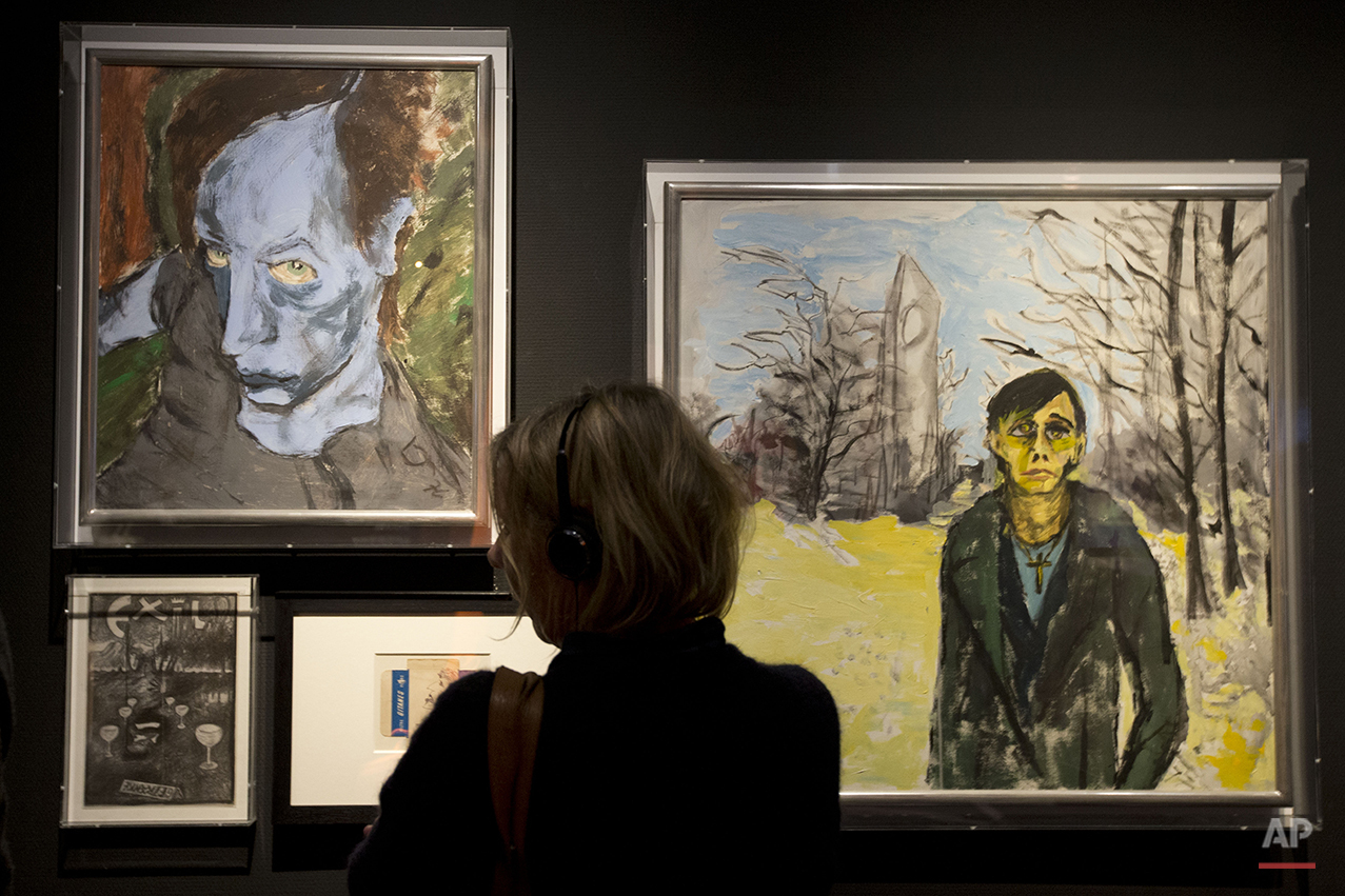 """A woman looks at paintings by deceased popstar David Bowie, the one at right of popstar Iggy Pop, at the Groninger Museum which hosts the """"DAVID BOWIE is' exhibit, in Groningen, northern Netherlands, Monday, Jan. 11, 2016. The museum is normally closed on Mondays but opened its doors to allow people to sign a condolence register and visit the Bowie exhibit which runs till March 13, 2016. (AP Photo/Peter Dejong)"""