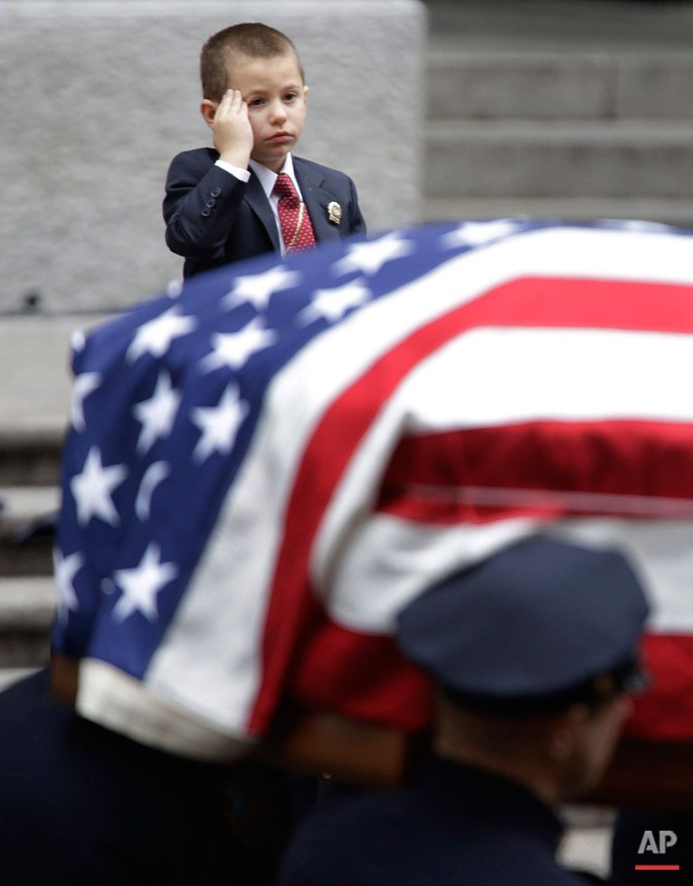 Ryan Lemm, 4, son of Joseph Lemm, salutes as his father's casket is carried out of St. Patrick's Cathedral in New York, Wednesday, Dec. 30, 2015. Lemm, who was a technical sergeant in the Air Guard's 105th Base Security Squadron and a 15-year veteran of the New York Police Department, was killed when his patrol was attacked by a suicide bomber outside Bagram Air Base in Afghanistan. (AP Photo/Seth Wenig)