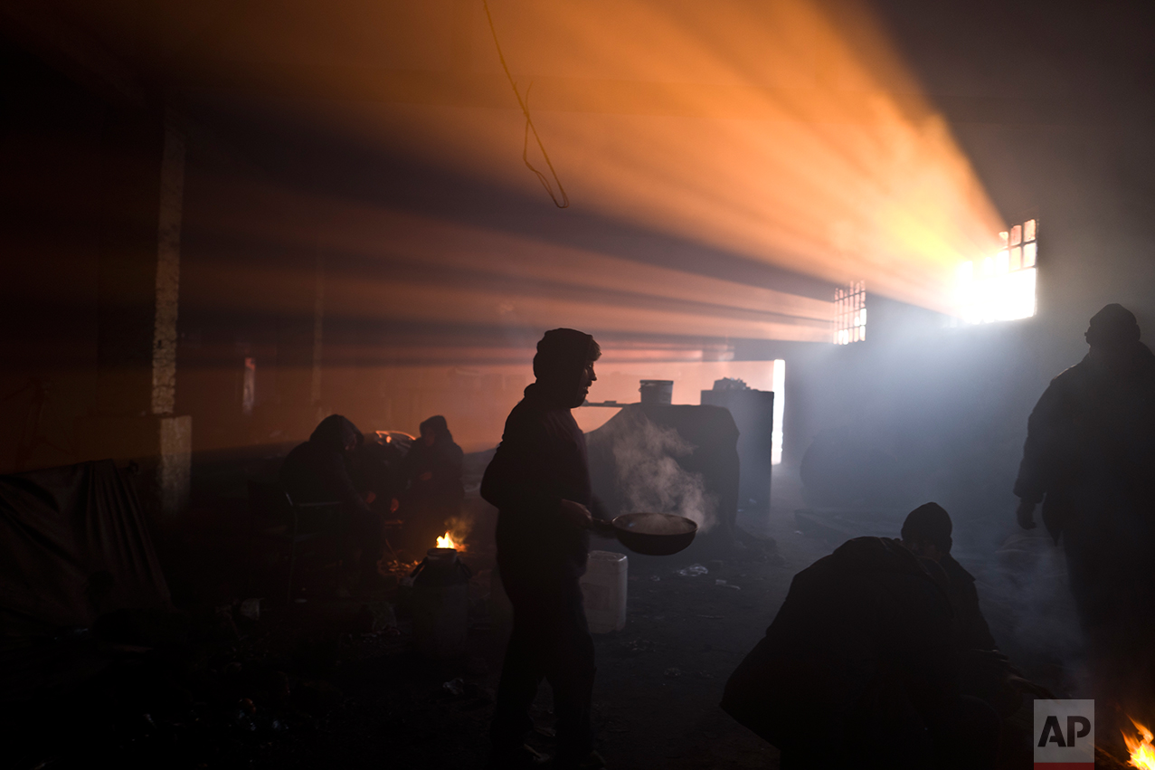An Afghan refugee man carries a pan while other migrants gather around a fire in an abandoned warehouse in Belgrade, Serbia, Monday, Jan. 30, 2017. (AP Photo/Muhammed Muheisen)