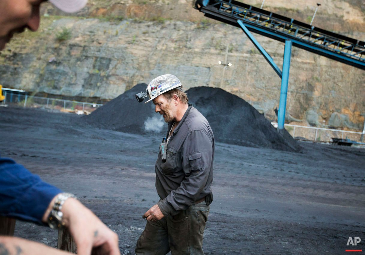"""Foreman John Dillon, a coal miner of 39 years, walks past piles of coal at the Sewell """"R"""" coal mine Tuesday, Oct. 6, 2015, in Yukon, W.Va. In the U.S., where natural gas has become a cheaper alternative to coal to generate electricity, miners are facing an especially difficult market: Four major U.S. coal companies have filed for bankruptcy protection in the last 18 months. (AP Photo/David Goldman)"""