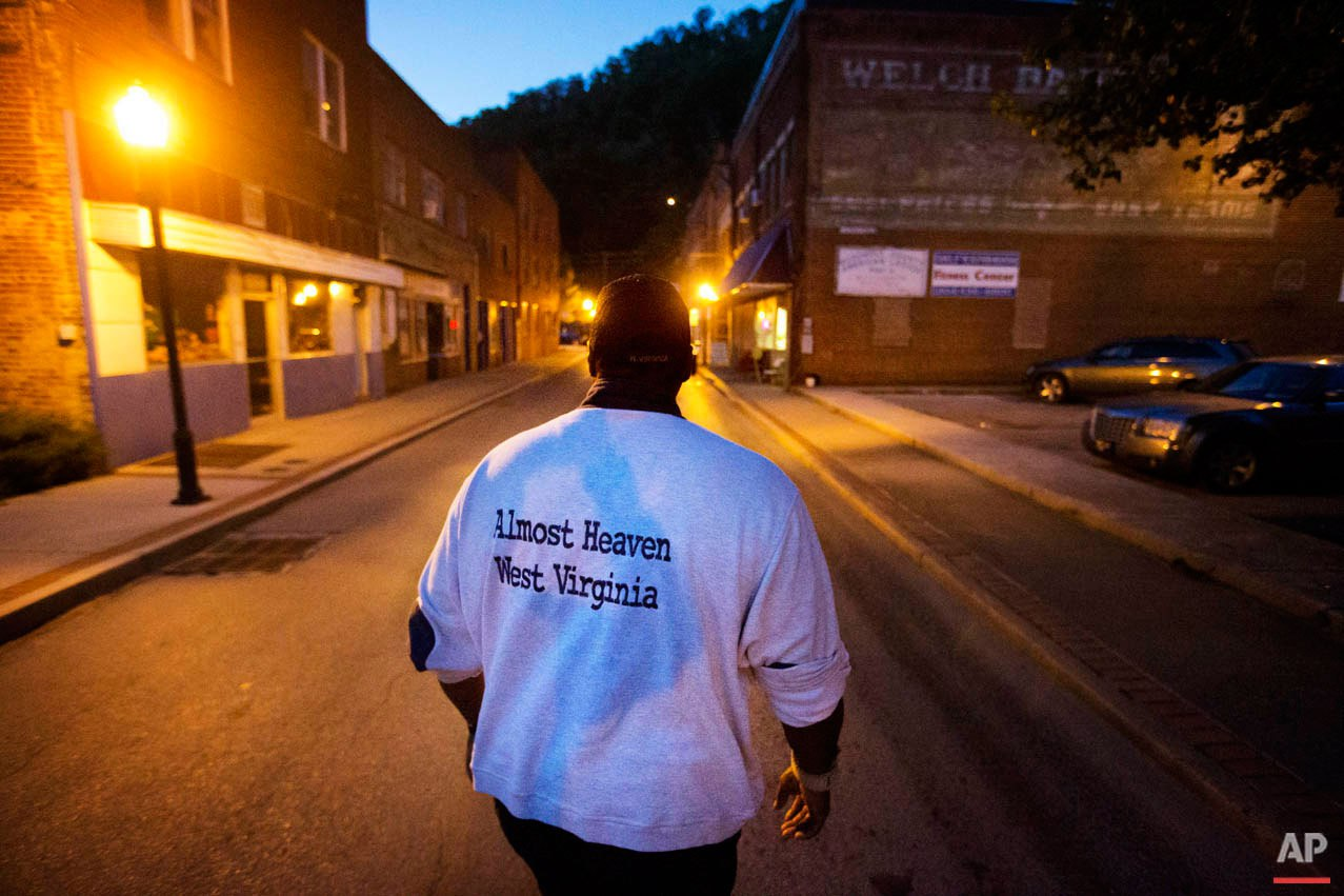 """Garnet Edwards Jr. walks through the street while volunteering for a nonprofit community organization in the business district Monday, Oct. 5, 2015, in Welch, W.Va. """"There's no place like home. We're always going to be here,"""" said Edwards, a native of Welch. """"All it takes is one person to keep caring."""" (AP Photo/David Goldman)"""