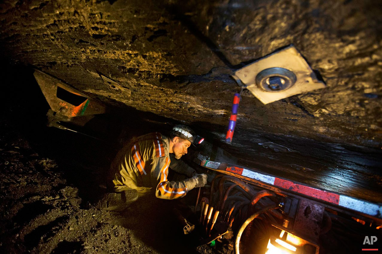 Scottie Stinson, a coal miner of 16 years, works to secure the roof with bolts in a coal mine roughly 40-inches-high, Tuesday, Oct. 6, 2015, in Welch, W.Va. The one main source for decent-paying work, the brutal life of coal, seems to be drying up for good. The thick, easy, cheap coal is gone, global competition is fierce, and clean air and water regulations are increasing costs and cutting into demand. But this crisis and the realization that there won't be another coal boom in these parts is leading to a growing understanding that new approaches are needed to help Central Appalachia emerge from decades of deep poverty, under-education and poor health. (AP Photo/David Goldman)