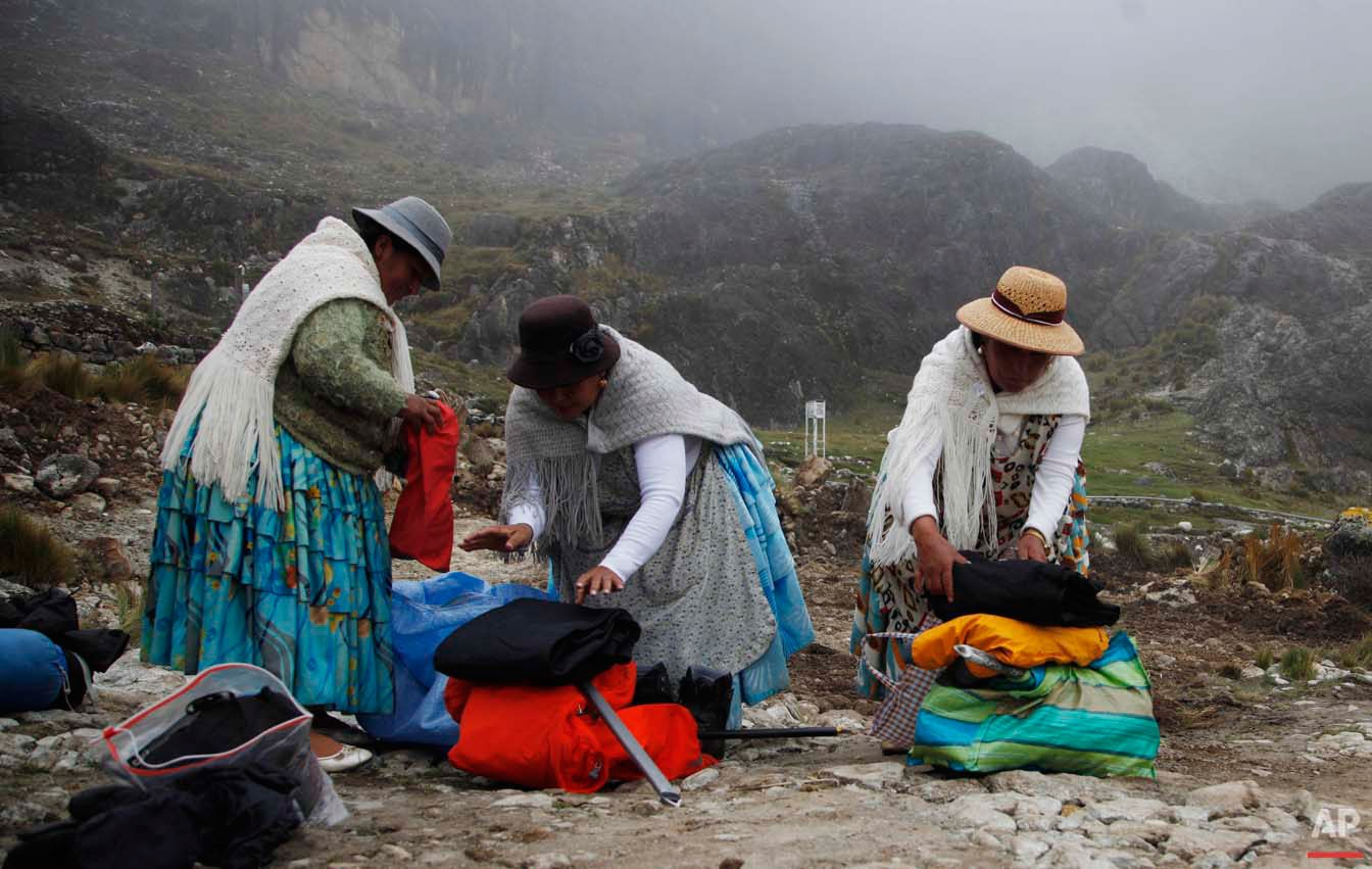 In this Dec. 16, 2015 photo, Aymara indigenous women, from right, Pacesa Alana Llusco, Dora Magueno Machaca and Bertha Vetia prepare their backpacks as they prepare to hike up the Huayna Potosi mountain on the outskirts of El Alto, Bolivia. Not letting their traditional, long multi-layered skirts get in the way, they put on their mountain gear and climbed one of the highest mountains in the country. (AP Photo/Juan Karita)