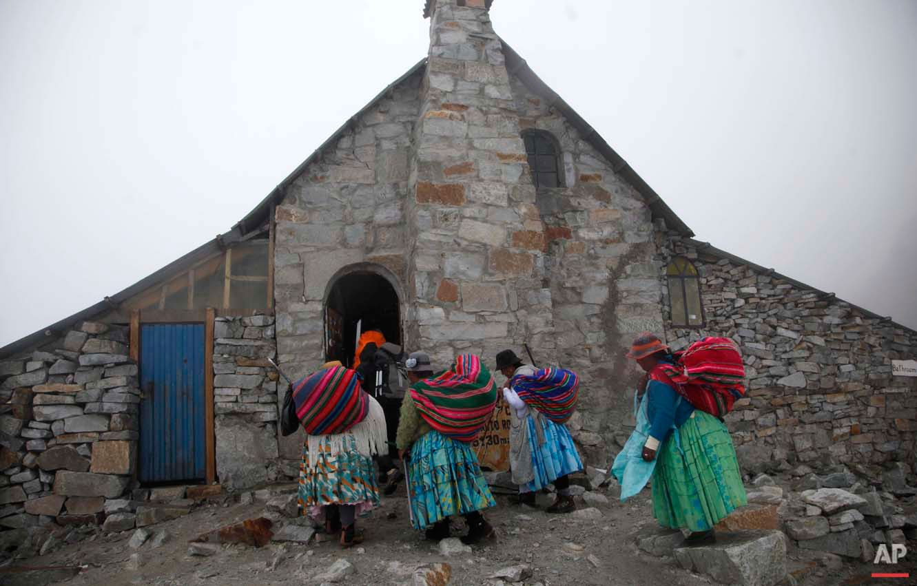 """In this Dec. 16, 2015 photo, Aymara indigenous women enter the Campo de Roca shelter for hikers as they climb the Huayna Potosi mountain on the outskirts of El Alto, Bolivia. Domitila Alana Llusco said she had a hard time finding appropriate gear she could afford when she started 15 years ago. """"My feet are small, there are no boots,"""" she said. """"But nothing stopped me and I have reached the peak of three mountains."""" (AP Photo/Juan Karita)"""