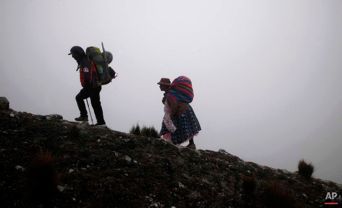 In this Dec. 16, 2015 photo, Aymara indigenous woman Cecilia Llusco Alana, right, follows her guide as they hike up the Huayna Potosi mountain on the outskirts of El Alto, Bolivia. They started the last piece of their ascent after midnight to take advantage of the hardness of the snow, hoping to reach the top by dawn. (AP Photo/Juan Karita)