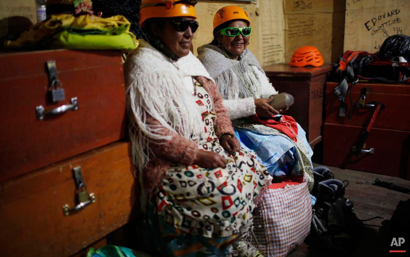 """In this Dec. 16, 2015 photo, Aymara indigenous women Lidia Huayllas, right, and Bertha Vetia sit after cooking dinner for their group of 11 female """"cholita"""" climbers inside the Campo de Roca shelter, before sleeping near the Huayna Potosi mountain on the outskirts of El Alto, Bolivia. Along with their traditional """"cholita"""" clothing, they use helmets, polarized goggles and crampons attached to their shoes. When on duty at the base, Aymara women work as porters and cooks, earning 20 US dollars per day. (AP Photo/Juan Karita)"""