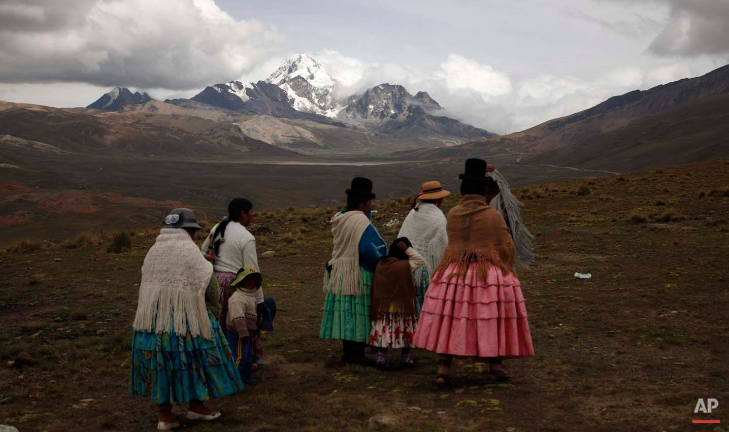 """In this Dec. 16, 2015 photo, Aymara indigenous women look at the Huayna Potosi mountain before climbing it on the outskirts of El Alto, Bolivia. At first glance, the women known as """"cholitas"""" don't look much like mountain climbers, with their colorful, multilayered skirts and fringed shawls, but they've been climbing for 15 years, cooking and carrying food for tourists who climb to the peak. (AP Photo/Juan Karita)"""