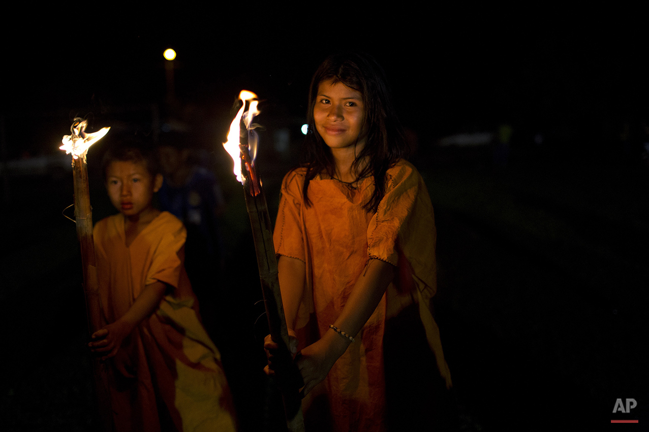 In this June 23, 2015 photo, Ashaninka Indian school children parade with torches during festivities celebrating the 44th anniversary of their village, in Otari Nativo, Pichari, Peru. The village is located in a valley near the Apurimac, Ene and Mantaro rivers in the world's largest coca growing region. (AP Photo/Rodrigo Abd)