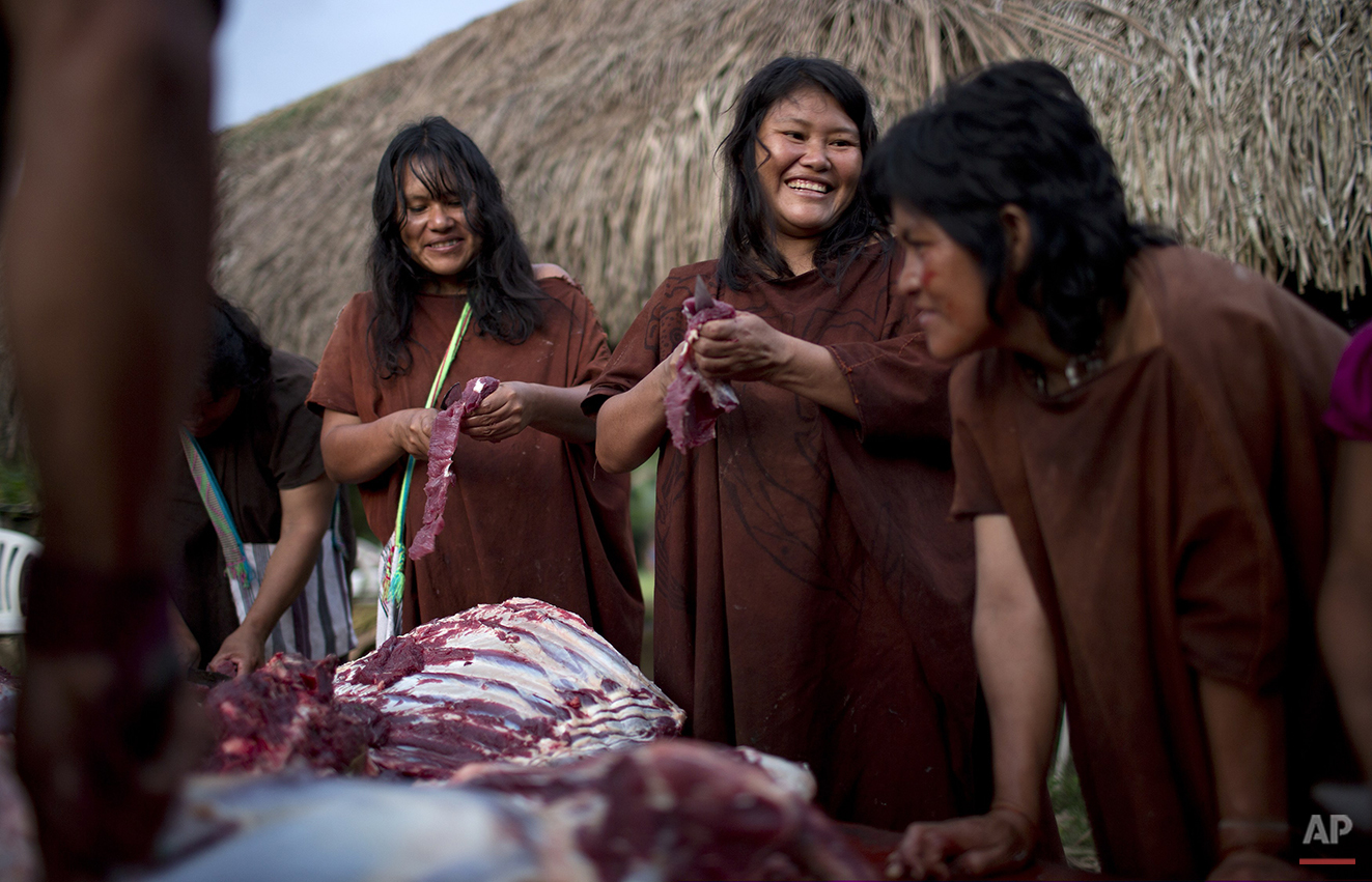 In this June 22, 2015 photo, Ashaninka Indian women skim fat from the meat of a cow in the village Otari Nativo, Pichari, Peru. The cow was donated by municipal authorities to mark the 44th anniversary of the community's founding. The community's men then smoked the large amounts of meat for festival-goers to consume. (AP Photo/Rodrigo Abd)