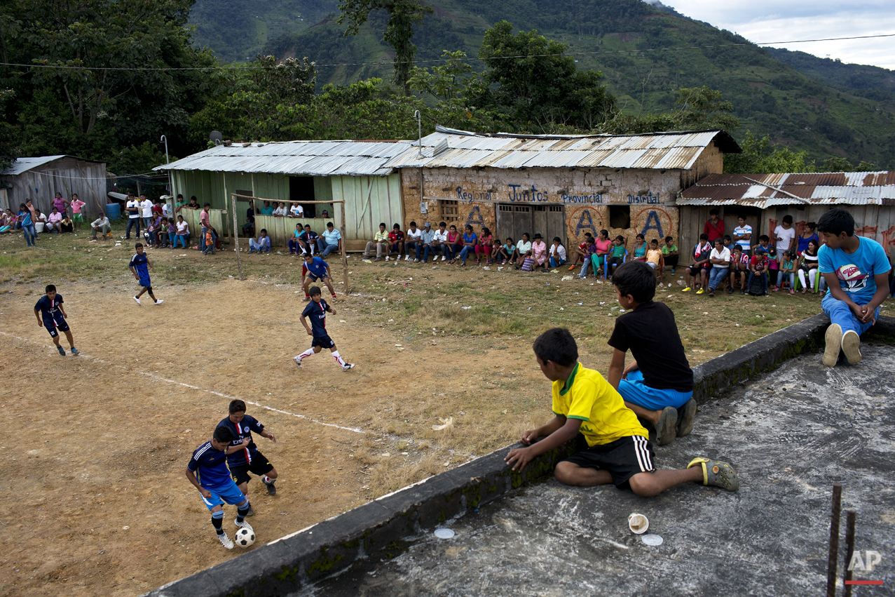 In this March 15, 2015 photo, young men compete in a multi-village soccer tournament, in La Mar, province of Ayacucho, Peru. A hardy lot, cocaine backpackers are mostly native Quechua speakers and hail from the isolated communities that suffered the worst atrocities of Peru's 1980-2000 dirty war with Shining Path rebels. (AP Photo/Rodrigo Abd)