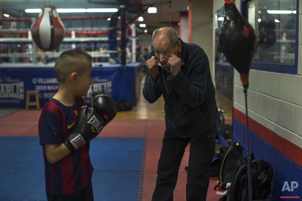 In this Monday, April 25, 2016 photo, boxing coach Manolo del Rio, right, talks to his young pupil Mario Andres Ciobanu, 8, during a training session at El Rayo boxing gym in Madrid. (AP Photo/Francisco Seco)