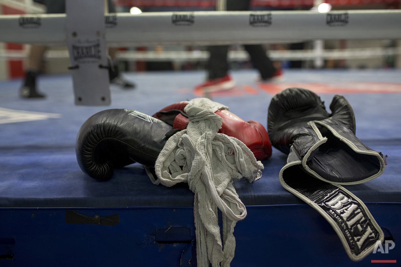 In this Friday, April 29, 2016 photo, boxing gloves lie on a boxing ring as boxers work out at El Rayo boxing gym in Madrid. (AP Photo/Francisco Seco)