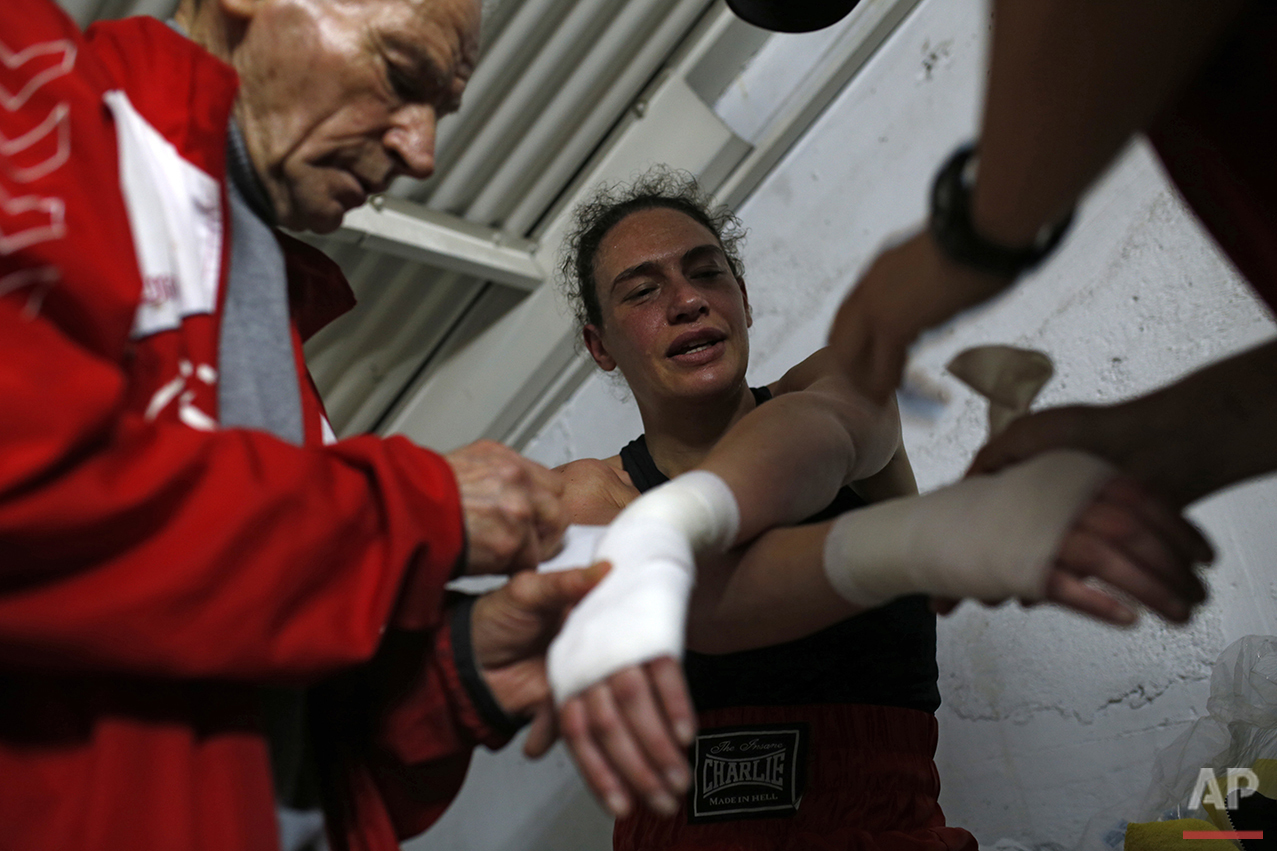 In this Saturday, April 23, 2016 photo, boxing coach Manolo del Rio, left, takes off a bandage from the hands of his pupil Esther Alcarazo, 32, after a boxing fight at El Rayo boxing gym in Madrid. (AP Photo/Francisco Seco)