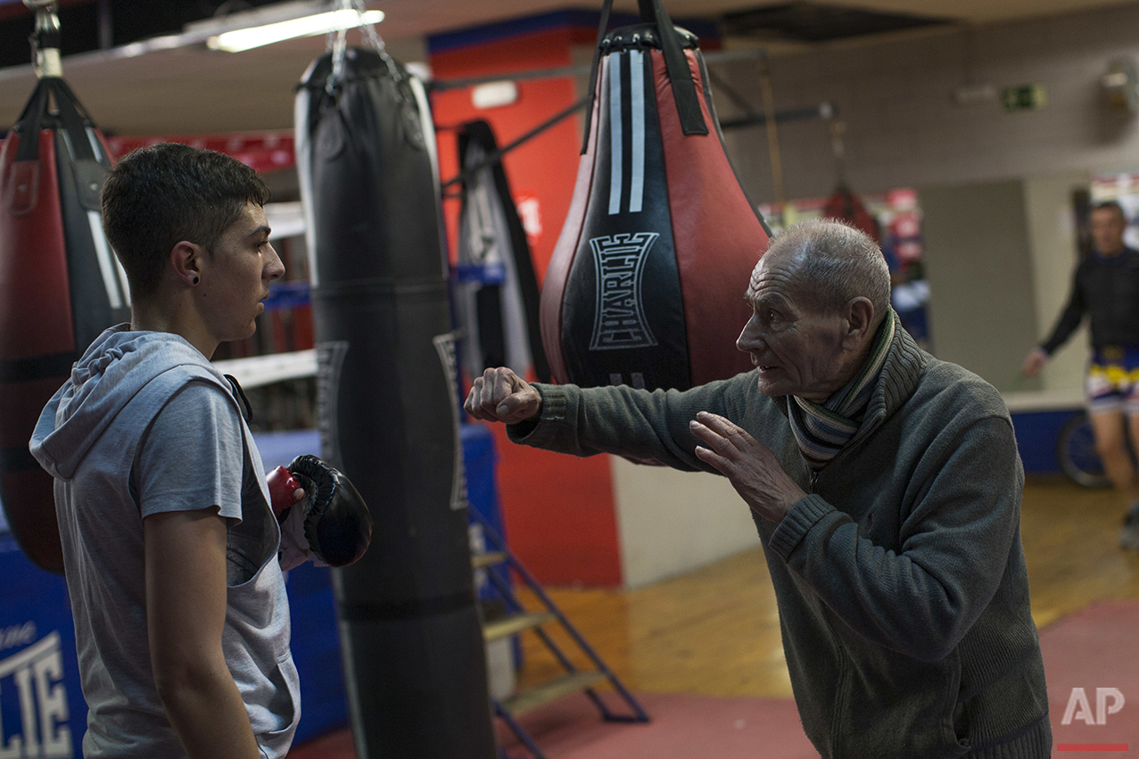 In this Friday, April 22, 2016 photo, boxing coach Manolo del Rio, right, talks to one of his pupils during a training session at El Rayo boxing gym in Madrid. At 84, Manolo del Rio is something of a legend in Spanish boxing circles, having spent more than 65 years training some of the country's best fighters and pledging to keep on going until he drops. He spends 12-14 hours a day at the gym in a working class neighborhood of Madrid. (AP Photo/Francisco Seco)