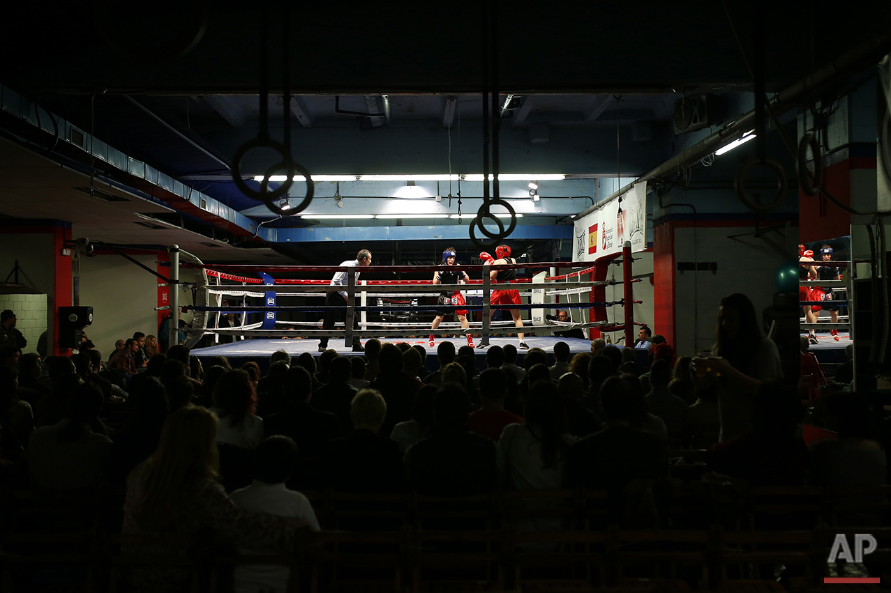 In this Saturday, April 23, 2016 photo, boxer Esther Alcarazo, top right, competes during a boxing fight at El Rayo boxing gym in Madrid. (AP Photo/Francisco Seco)