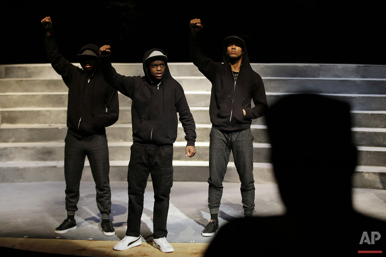 In this Tuesday, May 10, 2016, photo, actors Stanley Morrison, from left, Amir Randall and Julian Darden act out a scene as director Rajendra Ramoon Maharaj watches during a rehearsal for The Ballad of Trayvon Martin at the New Freedom Theatre in Philadelphia. The play, about the death of 17-year-old Trayvon Martin, opens Thursday. (AP Photo/Matt Slocum)