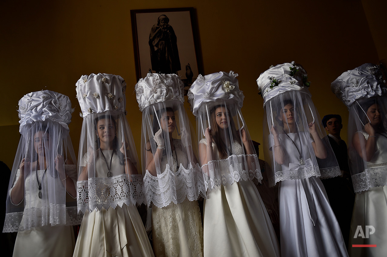 Participnats in the ''Bread Procession of the Saint'' take part in a ceremony in honor of Domingo de La Calzada Saint (1019-1109), in Santo Domingo de La Calzada, northern Spain, Wednesday, May 11, 2016. Every year during spring season, ''Las Doncellas'' (White Virgins), hold a basket on their head covered with white cloth while they walk along this old village in honor of the saint. (AP Photo/Alvaro Barrientos)