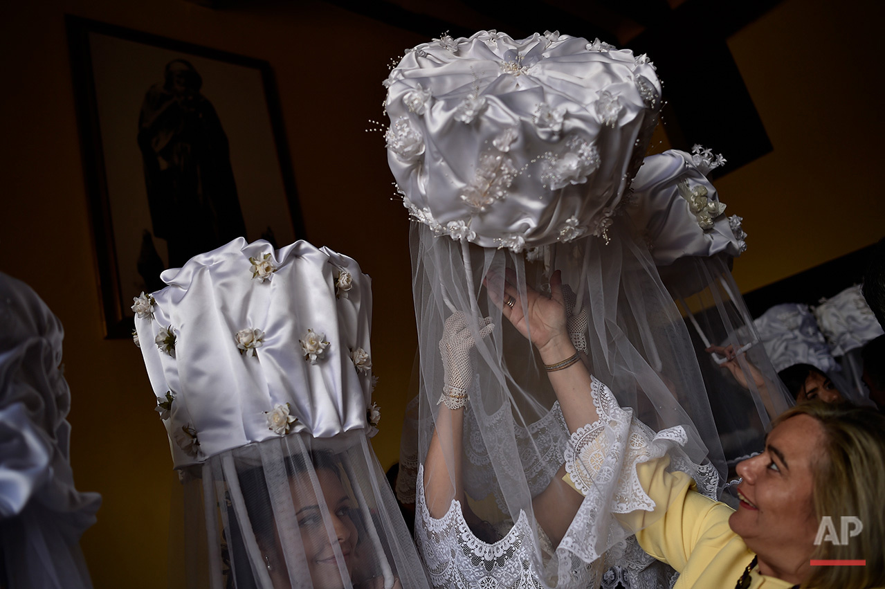 A participant of ''Bread Procession of the Saint'', is helped as she takes part in the ceremony in honor of Domingo de La Calzada Saint (1019-1109) in Santo Domingo de La Calzada, northern Spain, Wednesday, May 11, 2016.Every year during spring season, ''Las Doncellas'' (White Virgins), hold on their head a basket covered with white cloth while they walk through this old village in honor of the saint.  (AP Photo/Alvaro Barrientos)