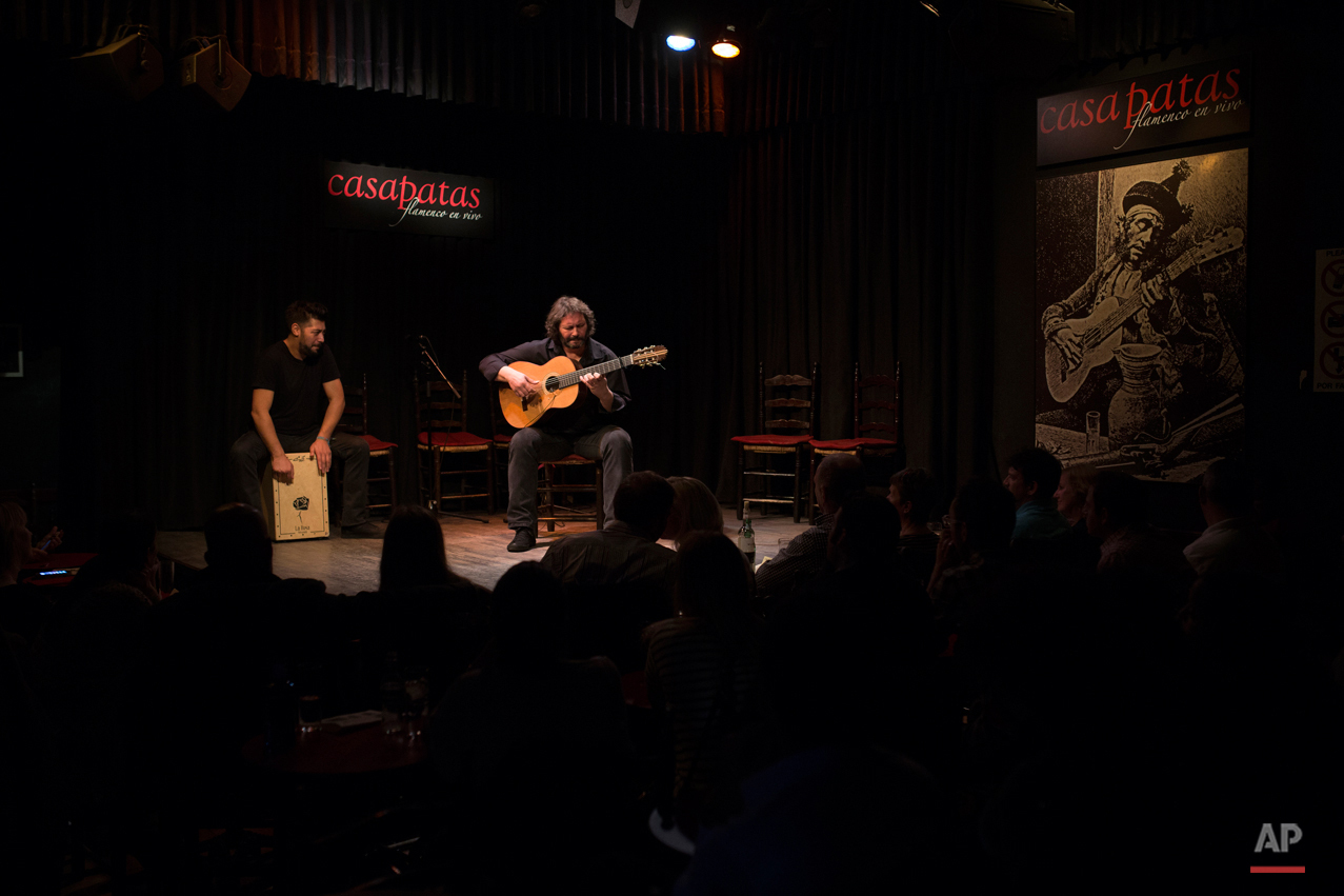 In this Wednesday, Nov. 11, 2015 photo, Spanish 'flamenco' guitarist Camaron de Pitita, right, performs with another artist during a show at the Casa Patas flamenco club in Madrid. Spanish flamenco guitars are known for their beautiful shape, rich wood colors and full-bodied, crisp musical tones. (AP Photo/Francisco Seco)