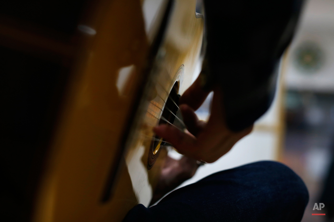 In this Wednesday, Nov. 11, 2015 photo, Spanish 'flamenco' artist Yoni Jimenez plays a guitar in a guitar workshop in Madrid. Spanish flamenco guitars are known for their beautiful shape, rich wood colors and full-bodied, crisp musical tones. (AP Photo/Francisco Seco)