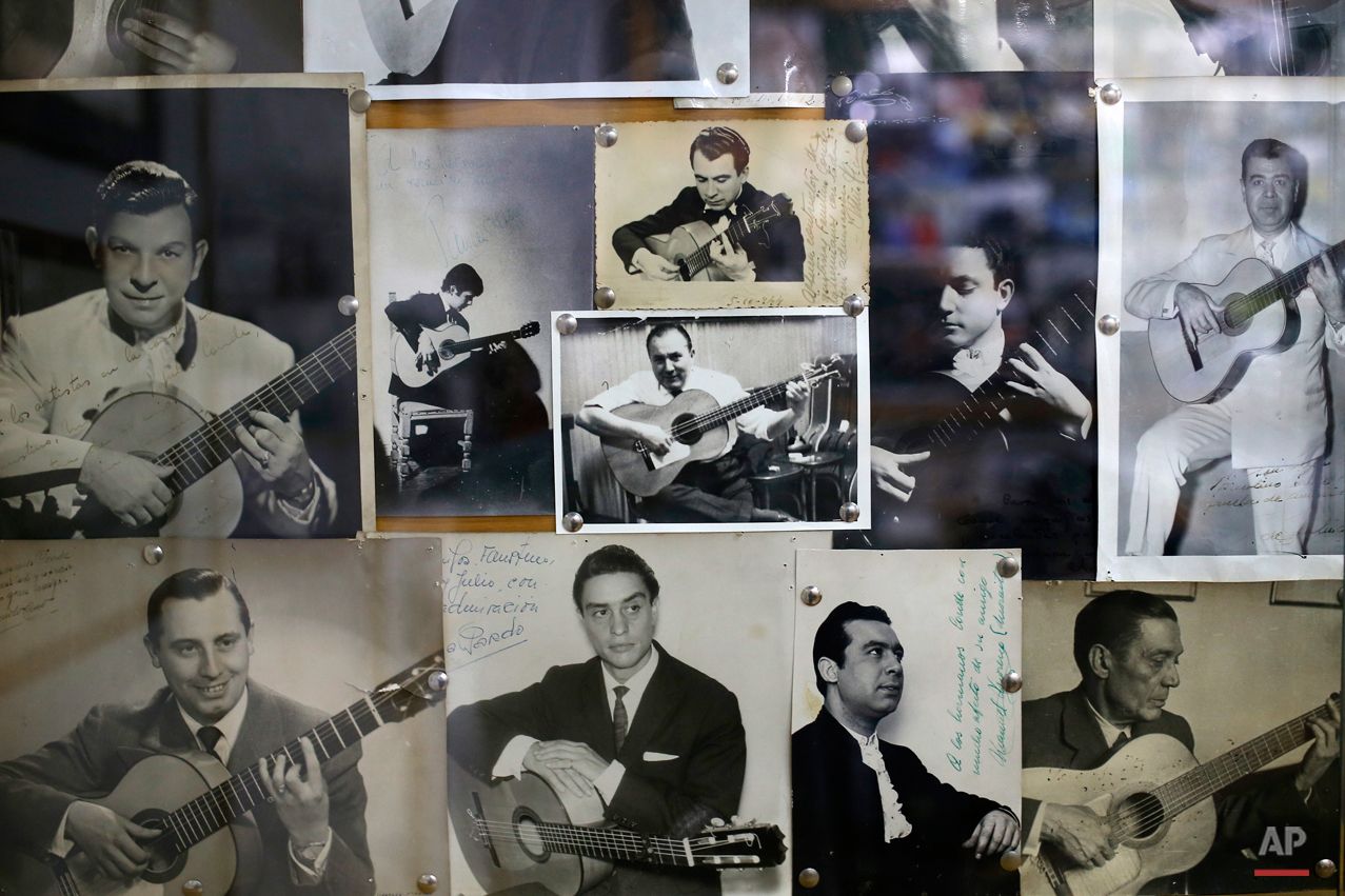 In this Wednesday, Nov. 11, 2015 photo,  photos of Spanish 'flamenco' guitar players are pinned to the wall at a guitar workshop in Madrid. Spanish flamenco guitars are known for their beautiful shape, rich wood colors and full-bodied, crisp musical tones. (AP Photo/Francisco Seco)