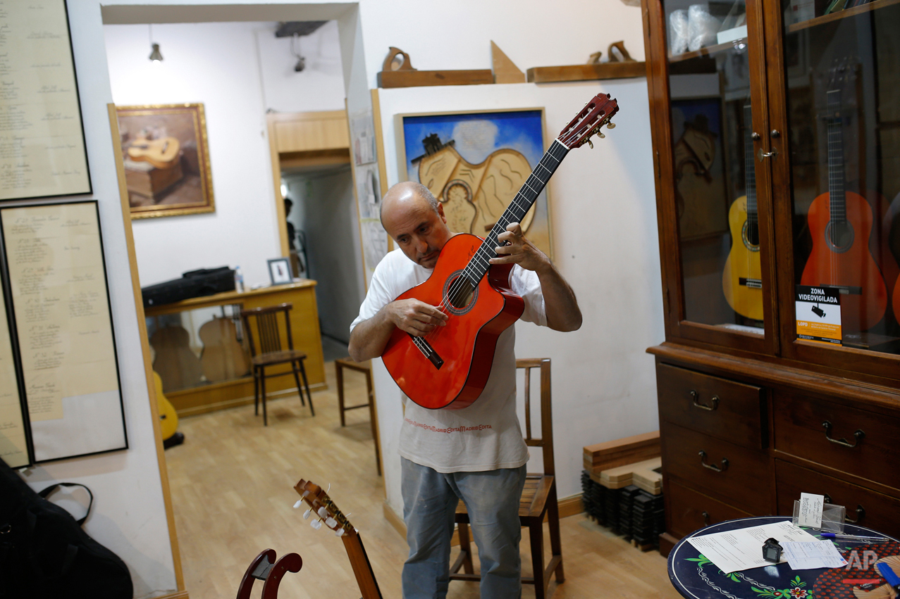 In this Wednesday, Nov. 11, 2015 photo, Spanish guitar maker Mariano Conde tunes a guitar at his workshop in Madrid. Carrying on the family tradition is Mariano Conde, who operates out of his workshop in downtown Madrid where and he and his son, also called Mariano, build their hand-made, individually sounding, classical and flamenco guitars. Spanish flamenco guitars are known for their beautiful shape, rich wood colors and full-bodied, crisp musical tones. (AP Photo/Francisco Seco)