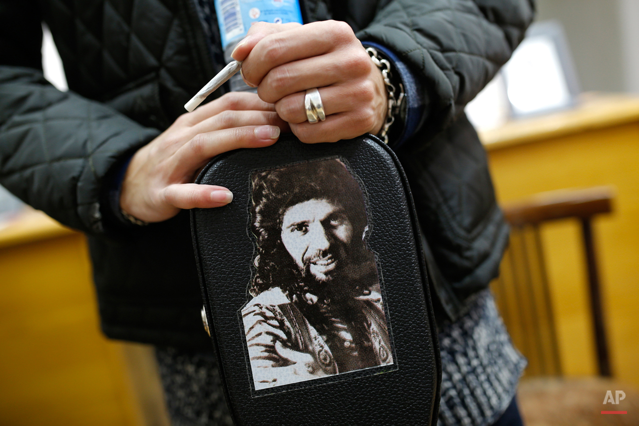 """In this Wednesday, Nov. 11, 2015 photo, Spanish 'flamenco' artist Yoni Jimenez rests his hands on his guitar case decorated with a photo of 'flamenco' icon singer """"Camaron de la Isla"""" at a guitar workshop in Madrid. Spanish flamenco guitars are known for their beautiful shape, rich wood colors and full-bodied, crisp musical tones. (AP Photo/Francisco Seco)"""
