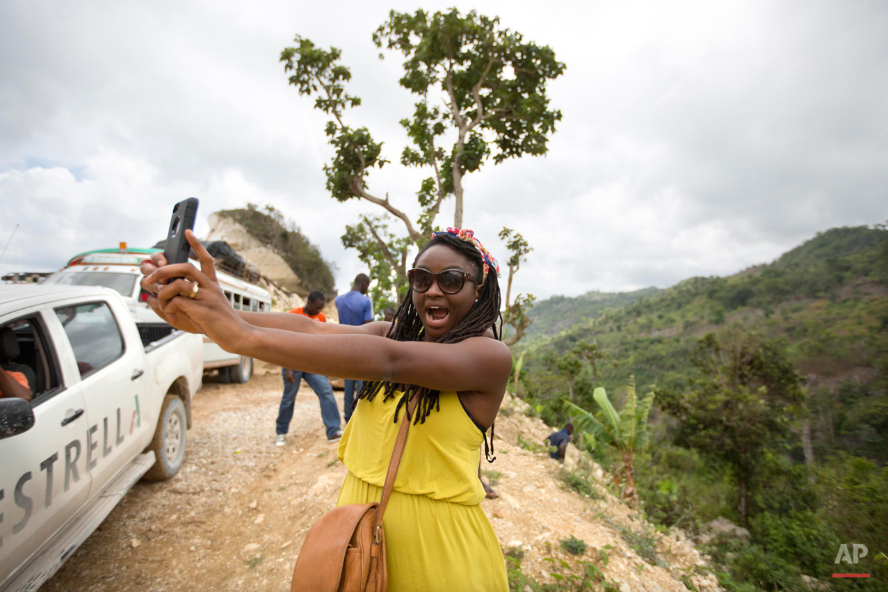 In this July 15, 2015 photo, adoptee Mariette Williams takes a selfie in Deron, a neighborhood on the outskirts of Pestel, Haiti. Mariette, who was adopted by a Canadian couple in October 1986, was recently reunited with her birth mother, Cola Etienne, who lives in Deron. ìEvery single day for my entire life I have always thought of my mom,î she said. ìWhen I wake up now I have a face to put to the name.î (AP Photo/Dieu Nalio Chery)