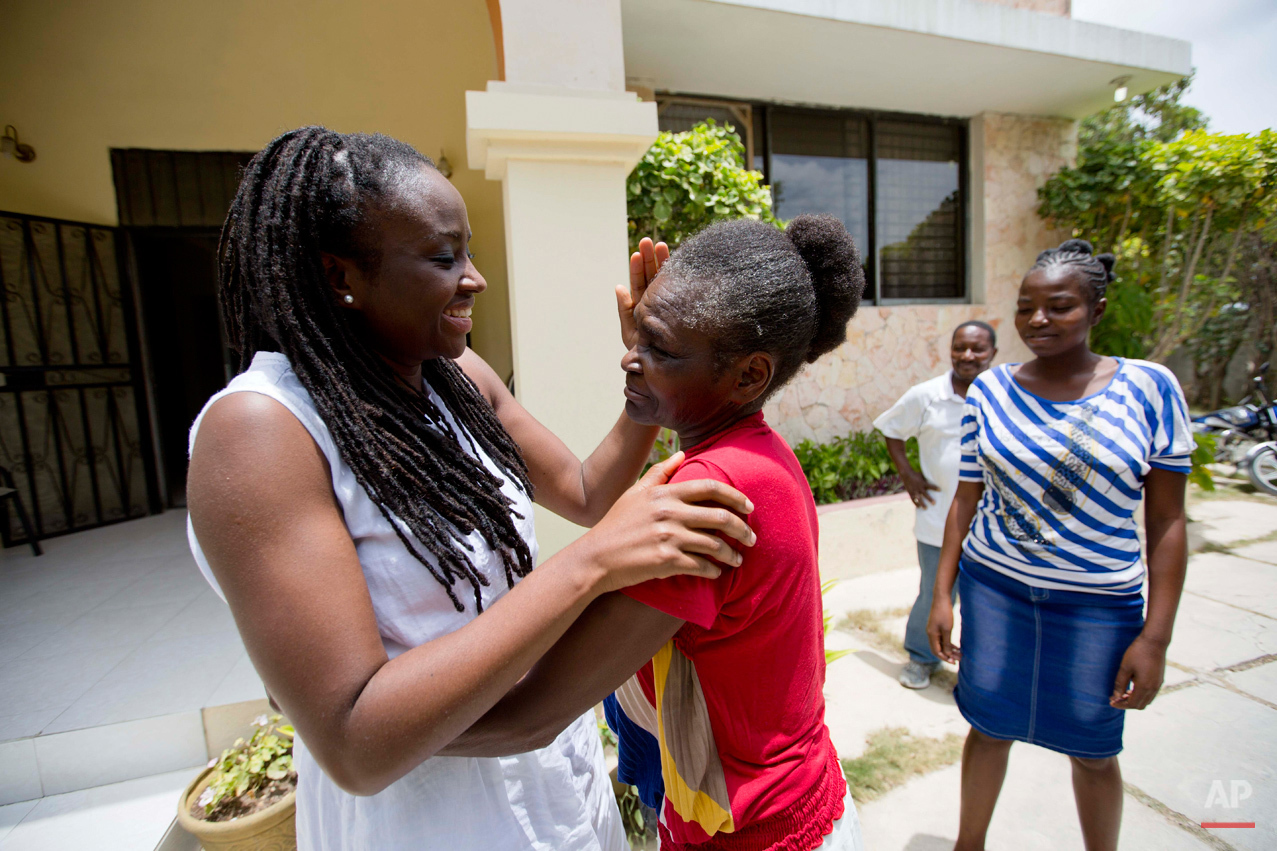 In this July 13, 2015 photo, Mariette Williams and her birth mother Colas Etienne, embrace for the first time in nearly 30 years, in Port-au-Prince, Haiti. Mariette, who had been adopted as a toddler and taken to Canada in 1986, bit by bit gathered her motherís story, how she had 10 children, seven of them still alive, and earned money from selling vegetables. (AP Photo/Dieu Nalio Chery)