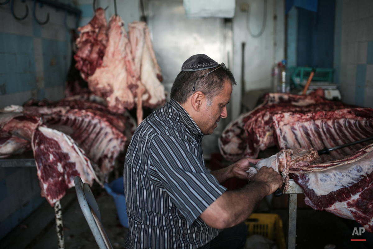 In this Wednesday, Oct. 28, 2015 photo, Char Haddad, 45, prepares meat in his kosher slaughterhouse at Hara Kbira, the main Jewish neighborhood on the Island of Djerba, southern Tunisia. The surrounding streets include a kosher butcher, a bakery that sells a traditional tuna-filled pastry known as ìbrikî and schools that teach lessons in Hebrew, French and Arabic. (AP Photo/Mosa'ab Elshamy)