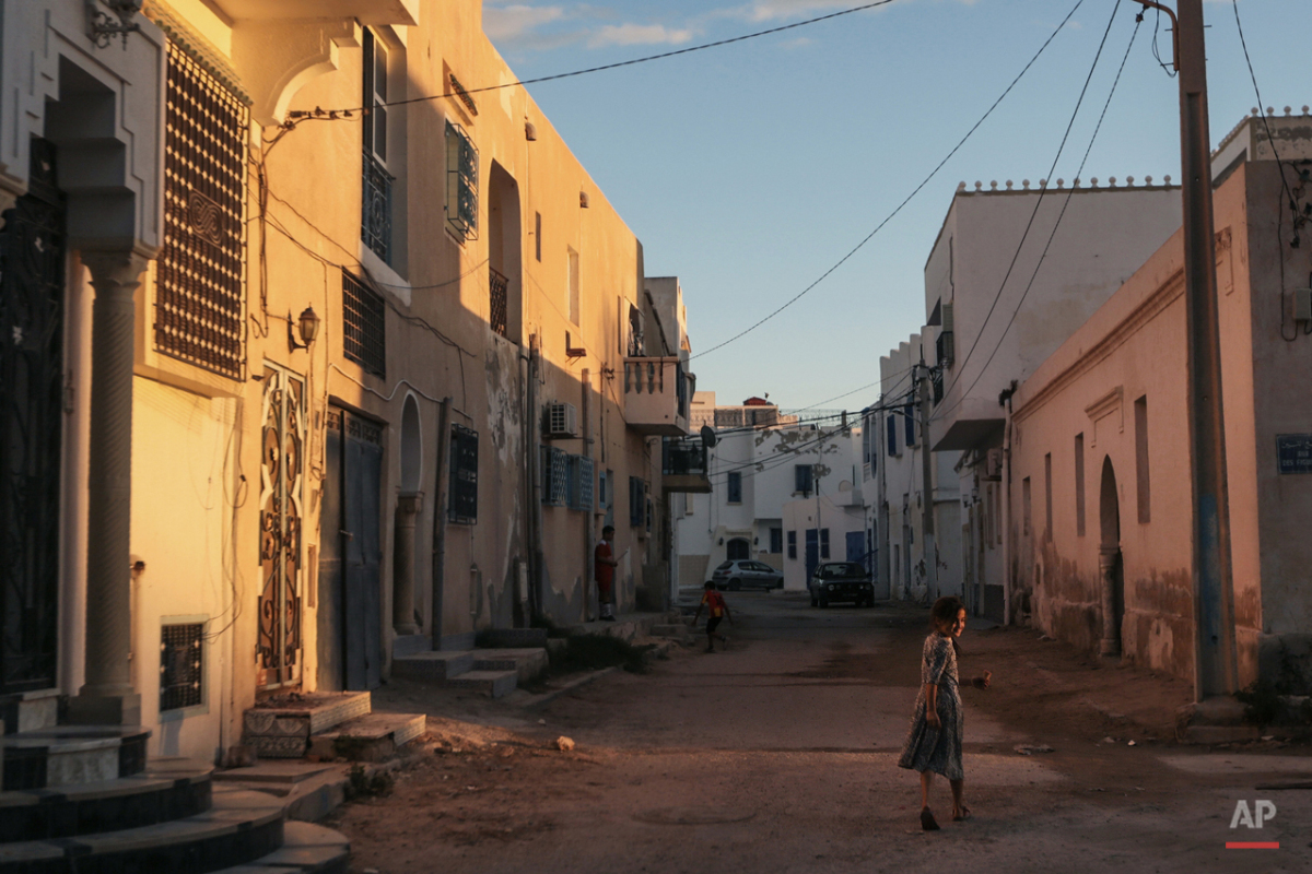 In this Friday, Oct. 30, 2015 photo, a girl walks home after sunset, at Hara Kbira, the main Jewish neighborhood on the Island of Djerba, southern Tunisia. The Jewish community in the resort island of Djerba traces its roots all the way back to Babylonian exile of 586 B.C., and is one of the few communities of its kind to have survived the turmoil around the creation of Israel, when more than 800,000 Jews across the Arab world either emigrated or were driven from their homes. (AP Photo/Mosa'ab Elshamy)