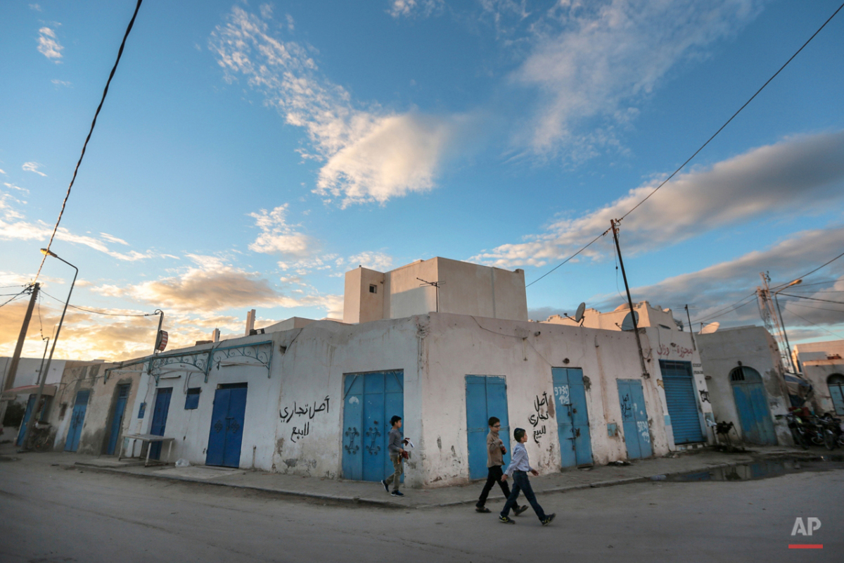In this Friday, Oct. 30, 2015 photo, boys walk past closed shops on the beginning of Shabbath, after sunset, at Hara Kbira, the main Jewish neighborhood in the Island of Djerba, southern Tunisia. The Jewish community on the resort island of Djerba traces its roots all the way back to Babylonian exile of 586 B.C., and is one of the few communities of its kind to have survived the turmoil around the creation of Israel, when more than 800,000 Jews across the Arab world either emigrated or were driven from their homes. (AP Photo/Mosa'ab Elshamy)